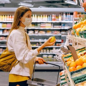 Woman in yellow tshirt and beige jacket holding a fruit 3962285 3